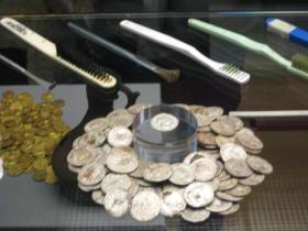 A close up of the silver denarii and conservator's cleaning tools!