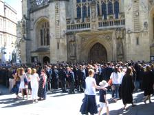 Parents and school youngsters gathering outside Bath Abbey.