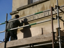 Mark Holland busy restoring the Sydney Place incised sign.