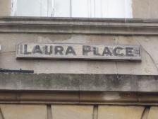 A modest wooden sign for Laura Place