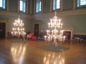 Two of the chandeliers in the ballroom lowered for cleaning.