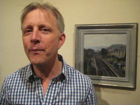 Artist Peter Brown - pictured next to one of his favourite works.  Oldfield Park Station 2013