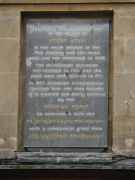 A memorial plaque giving the history of Pulteney Bridge and subsequent restorations. Now difficult to read.