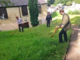 George Thomas and Rupert Bendell try their hand  at scything under the watchful eye of Pools  'guardian' Keith Williams