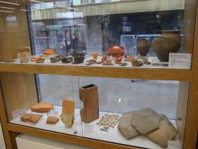 There are displays of Roman and Medieval remains in window display cases.