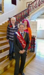 Bath & North East Council Chairman, Cllr Martin Veal (centre) wearing the knitted poppy sash, with Emma Leith and Rosie Wilks from the poppy knitting group.