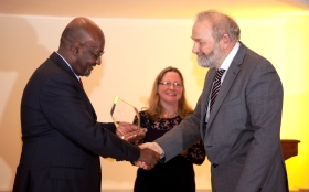 Mr Stephen Clews, Roman Baths Manager, receiving the award from Mr Getachew Engida, Deputy Director General of UNESCO, watched by Elizabeth Oxborrow-Cowan of UNESCO UK.