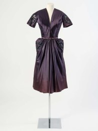 Hardy Amies Dark purple silk satin cocktail dress decorated with an oval shaped cutwork motif embroidered with beads, about 1950