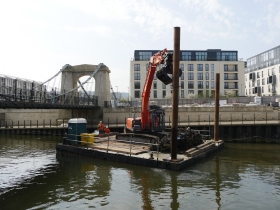 The pontoon-mounted crane in action by the Victoria Bridge.