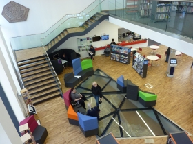 A view from the first floor of the One Stop Shop showing the distracting seating that has been placed overlapping the main panels of the mosaic from room W. Fortunately only two seats were occupied on this occasion. The great rosette from room J's mosaic may be seen on the staircase wall.