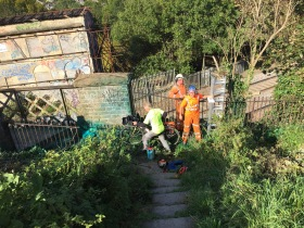 Contractors clearing vegetation and applying weed killer.