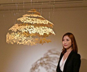 Nahoko Kojima and her paper cut sculpture in gold.