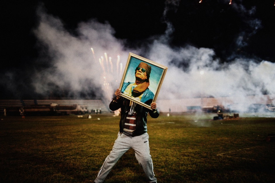 history-through-a-lens-moises-saman-libya-zawiyah-2011-a-qaddafi-supporter-holds-a-portrait-of-the-libyan-leader-during-a-celebration